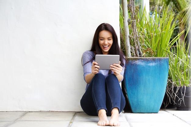 Счастливый молодая женщина, глядя на цифровой планшет и улыбается