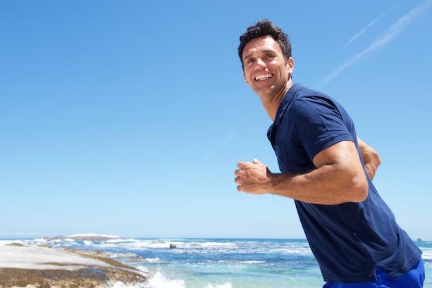 ビーチでカジュアルに走っているアクティブな男性