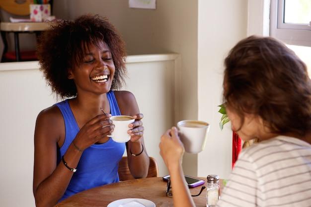 Две подружки наслаждаясь чашечкой кофе в кафе