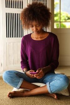 Молодая женщина, сидя на полу с мобильного телефона