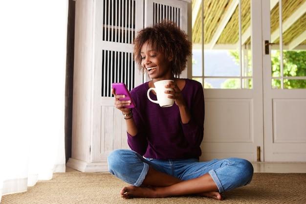 Улыбается черная женщина, сидя на полу у себя дома с мобильного телефона