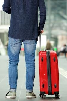Человек с дорожной сумкой, стоящей на вокзале