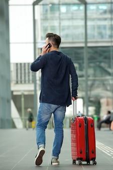 Человек разговаривает по мобильному телефону в аэропорту