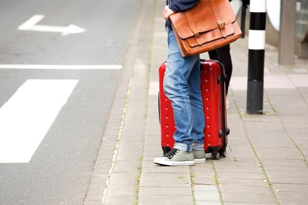 Мужчина-путешественник, стоящий на улице с чемоданом