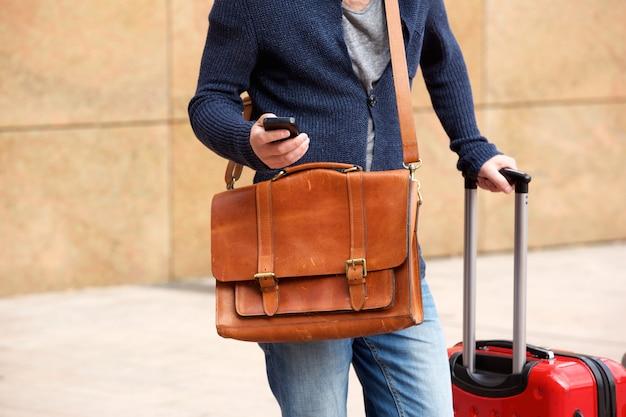男性の旅行者は、携帯電話とバッグで屋外に立って
