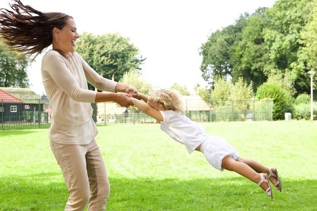 公園で幸せな若い母親のスイング娘の肖像画