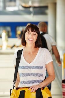 幸せな女性の旅行者は、袋と駅で歩いて
