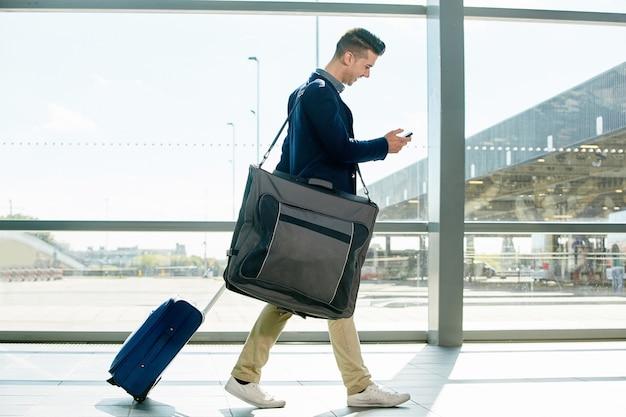 スーツケースと電話で駅で歩く幸せな男の全身の肖像画
