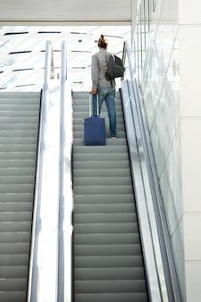 旅行のバッグでエスカレーターに立っている男