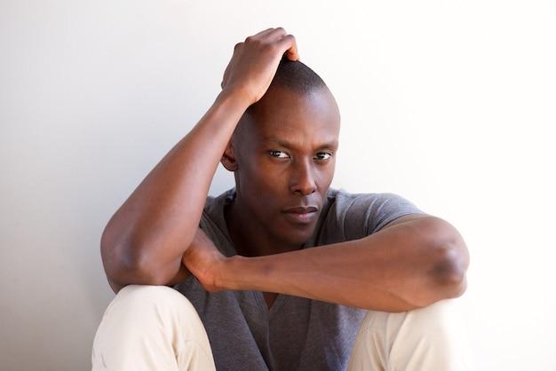 白い壁に座って考えているアフリカ系アメリカ人男性を閉じます