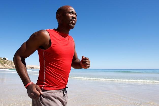 海岸に沿って走っている健康的な若いアフリカの男