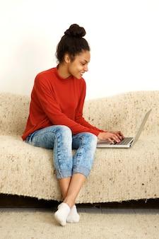 家でラップトップを使って笑顔の若い女性