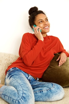 Молодая женщина улыбается и разговаривает по мобильному телефону у себя дома
