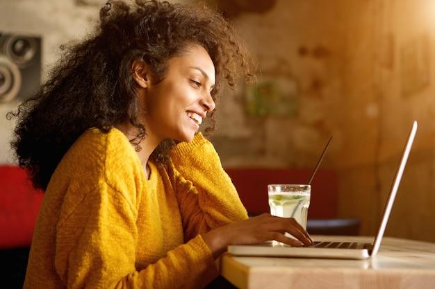 Веселая молодая женщина, работающая на ноутбуке в кафе