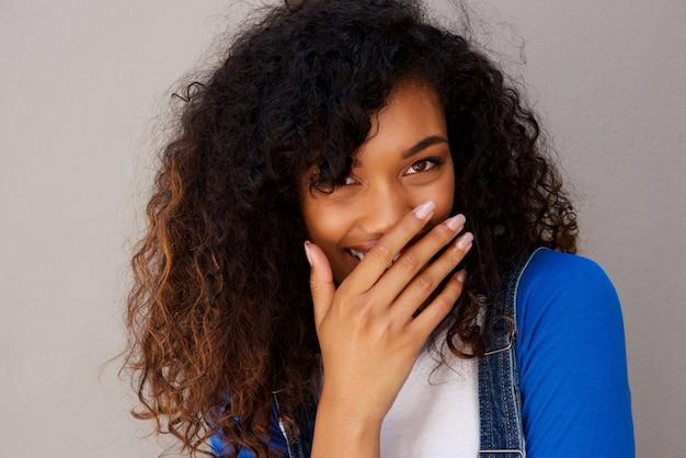 Счастливый молодая черная женщина хихикает против серой стены