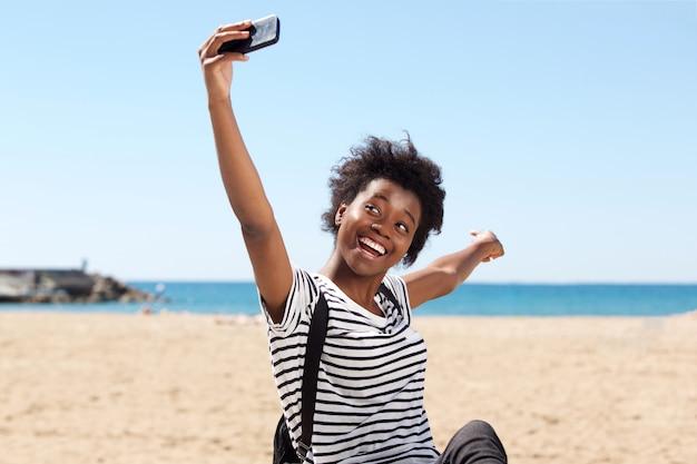 ビーチで若いアフロアメリカの女性を笑顔にしてセルフを話す