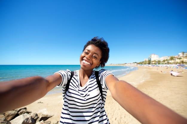 ビーチに立ってセルフを話す朗らかな若いアフロアメリカ人の女の子