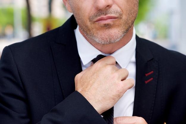 Закройте серьезный бизнесмен корректирующий узел на галстуке
