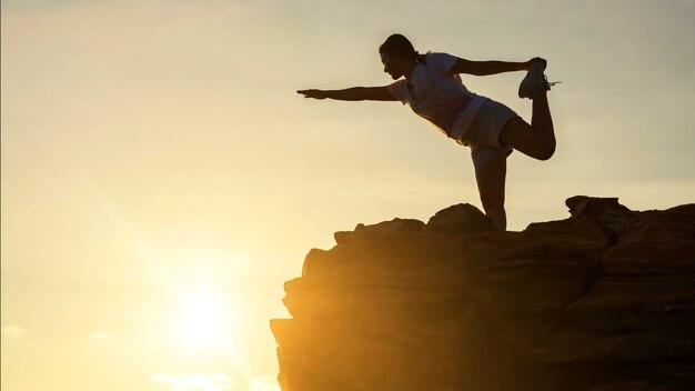 Силуэт спорта красивая женщина выполнять упражнения йоги на вершине холма во время заката