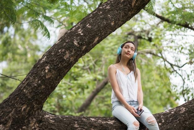 女の子は公園でストリーミング音楽を聞く