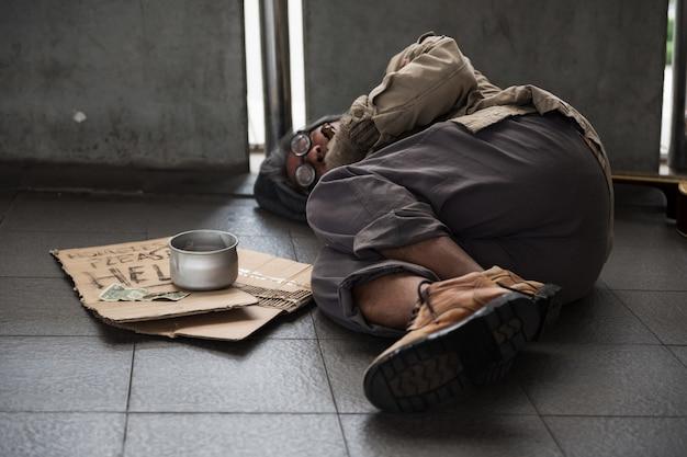 古いホームレスの男は歩道に寝る