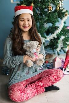 かわいい女の子がクリスマスツリーの近くにテディベアを演じる