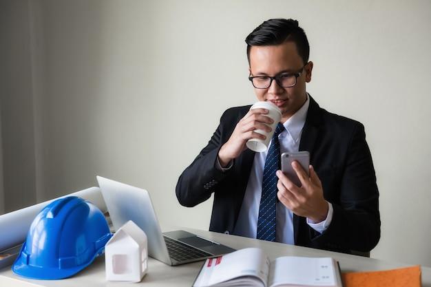 ビジネスマンはコーヒーを飲み、スマートフォンを演奏する