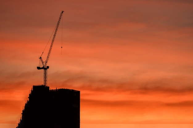 シルエットクレーンと夕暮れ時に建物の建設