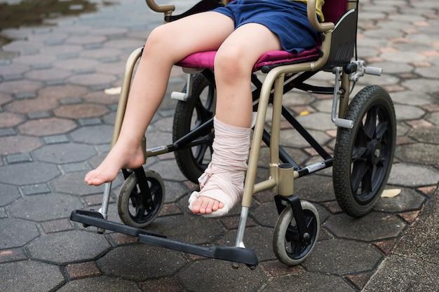 足の骨折した少年は車椅子に座る
