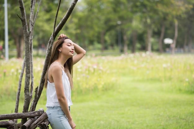 女性は夏の公園でリラックスします。