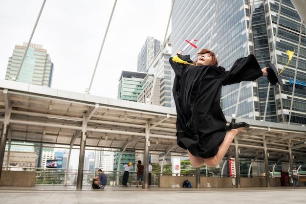 ガウンでアジアの大学院の女性が卒業証書とジャンプします。