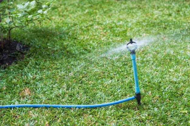 芝生のフィールドにスプレー水を振りかける