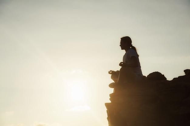 日没時に山の頂上でヨガ