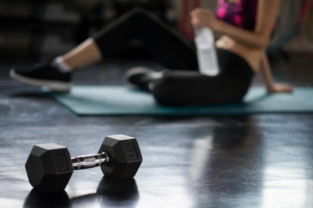 Перерыв женщины после тренировки гантели в спортзале