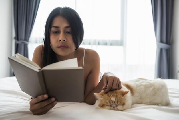 女性は本を読み、ベッドの上で猫を遊ぶ