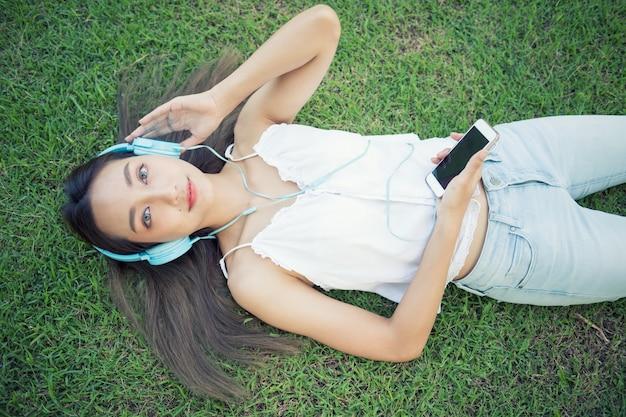 美しい少女は公園で音楽を聴く