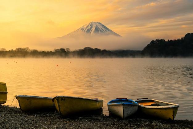 Лодки на озере седзи и горы. фудзисан на рассвете