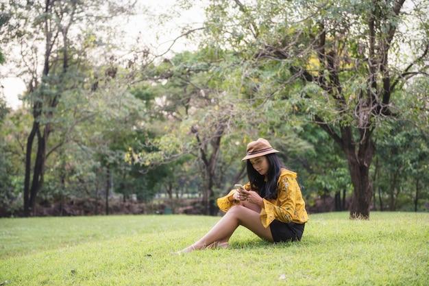 帽子を持つ少女は、公園でスマートフォンを再生します