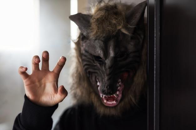 ハロウィーンパーティーのための怖いオオカミのマスクを持つモデル