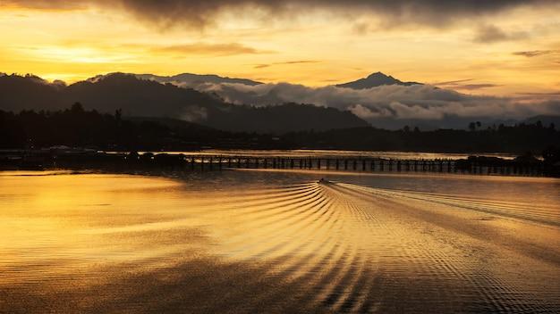 Лодка плывет к деревянному мосту, сангхлабури