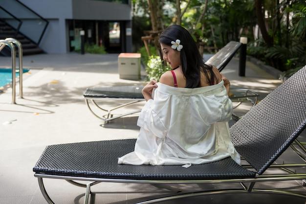 Женщина снимает платье в бассейне