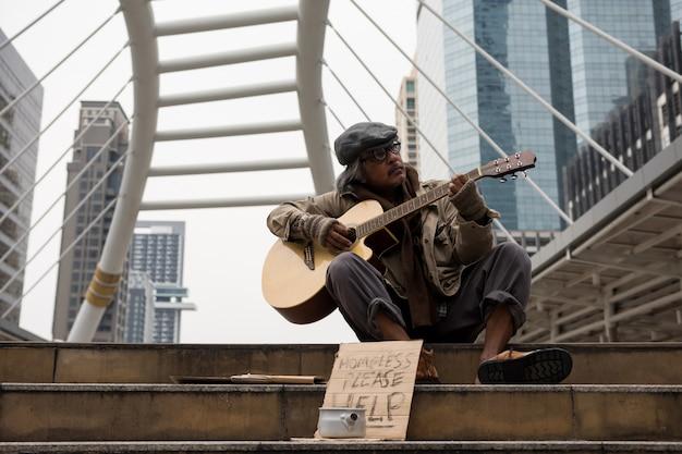 Старый нищий играет музыку на деньги