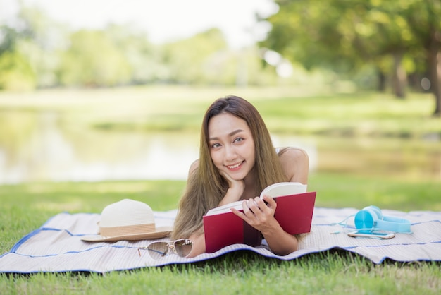 かわいい女性は夏の公園で本を読みます