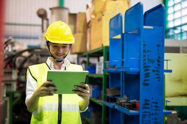Фабричный рабочий проверяет инвентарный запас на планшете