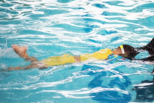 Мальчик ребенок практикует плавание с тренером