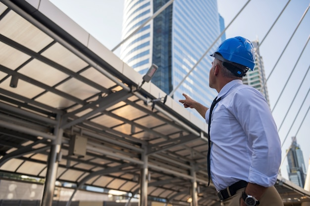 灰色の髪とヘルメットを持つ古いアメリカのエンジニアリングコンサルタントは、近代的な都市の建設現場の建物に指を向けます。