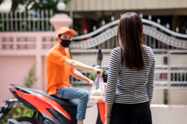 後部アジアの女性は、フェイスマスクを持つ宅配便の配達人がバイクに乗って家に到着する間、食べ物を待ちます。