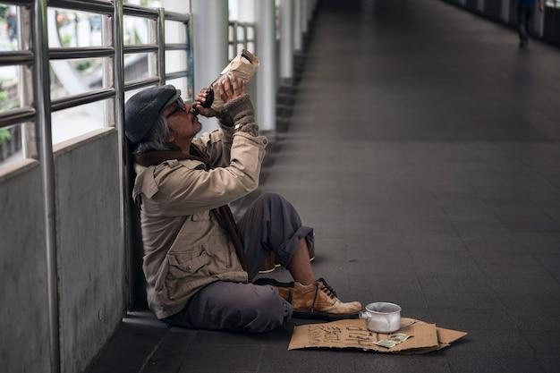 悲しいホームレスの老人がビールを飲む
