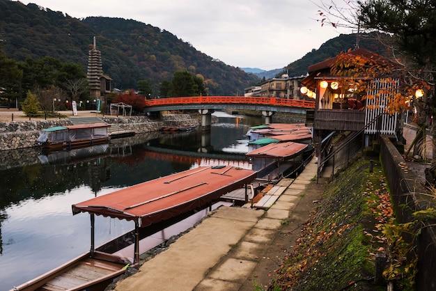 茶色の家と紅色の橋がある宇治川沿いの橋