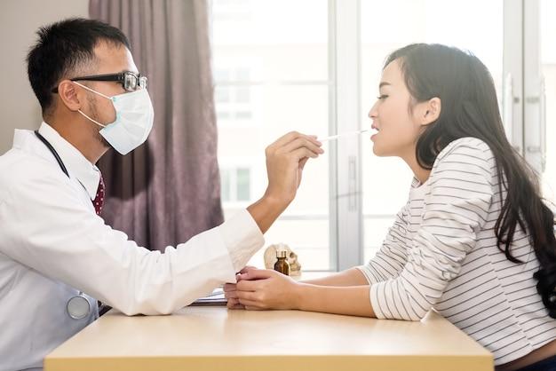 アジアの医師または医師は、扁桃腺と美しい女性の喉の痛みをチェックします。